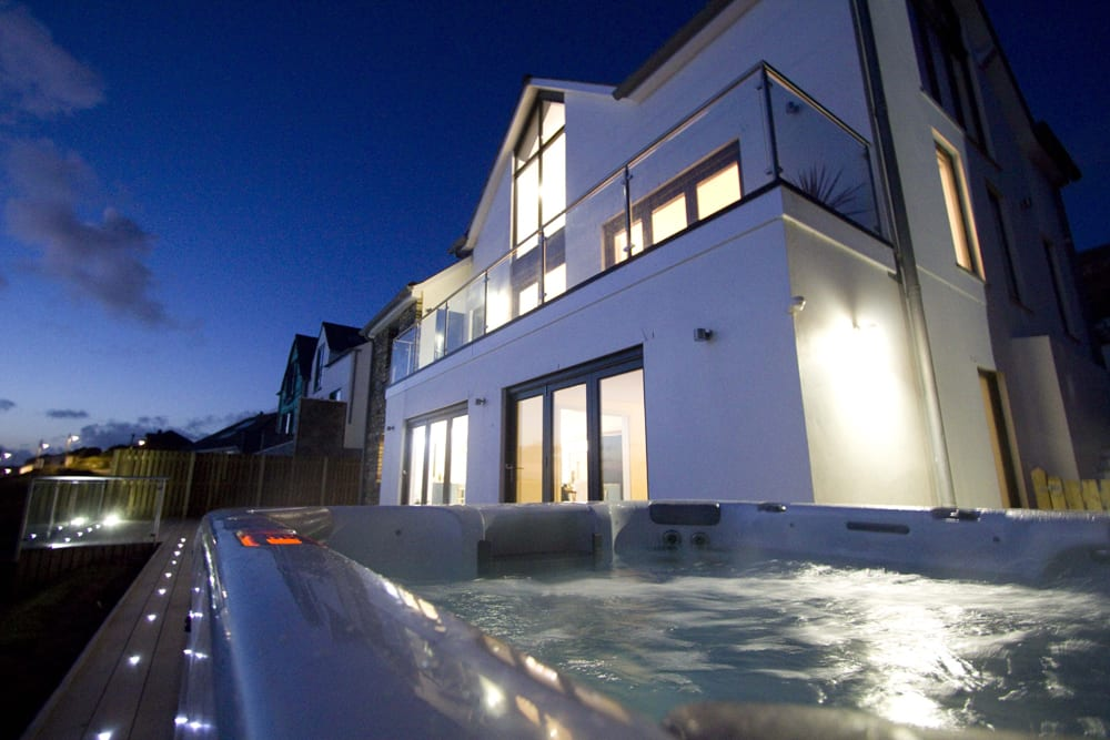 Image taken from hot tub outside at night, looking up to modern white house with glass balcony