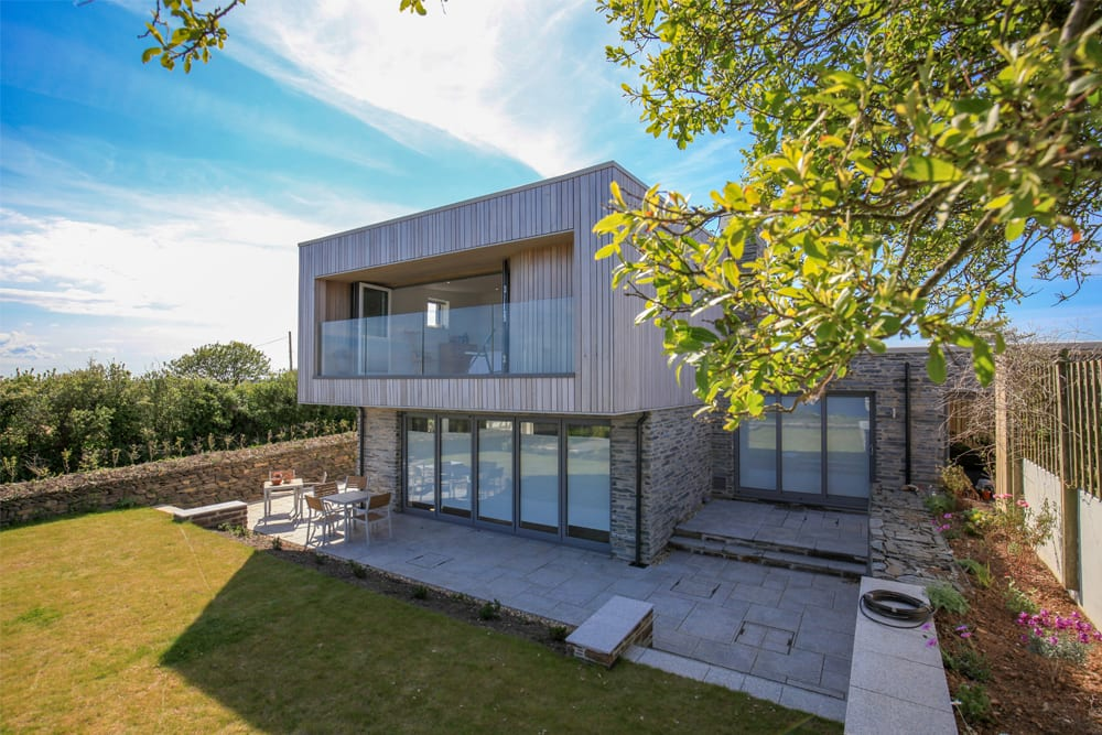 Modern house with overhanging 2nd floor, patio, glass doors and balcony and and grass