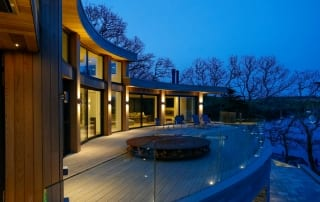 Large house at dusk with large balcony and glass railing