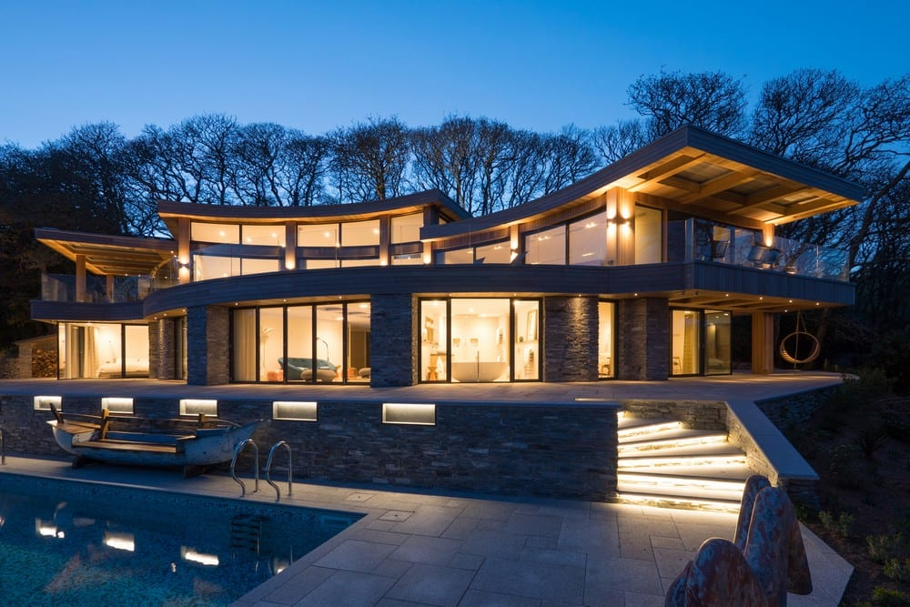 House at night with curve roof, large glass windows and swimming pool.