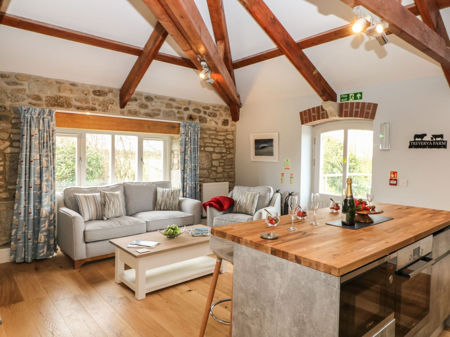 Living room kicthen interior with exposed stone wall and wooden beams.