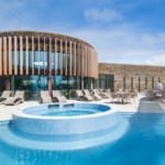 Curved luxury spa building design with outdoor pool and seating area